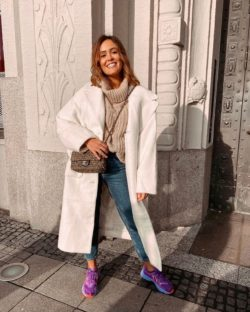 Women wears white coat, jeans and sneakers in a street