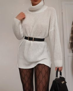 Girl wears white knitted turtle neck dress with a black waist belt, gucci tights and a black bag at home